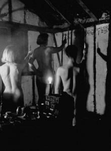 Bajo símbolos cabalísticos, las brujas desnudas elevan sus cuchillos rituales para invocar a sus dioses en una reunión. Su desnudez escandaliza a muchas personas, pero las brujas afirman que esto representa la separación de lo mundano.